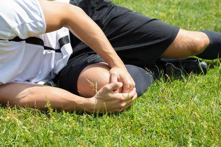 Nahaufnahme des männlichen Spielers, der unter der Knie-Verletzung liegt auf Feld leidet