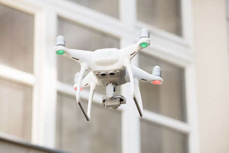 Low angle view of drone spying through house window Stock Photo