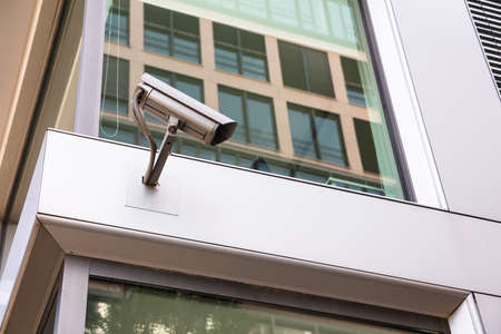 Low angle view of security camera mounted on office building in city