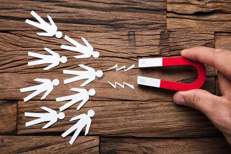 Closeup di magnete attirando candidati di carta sul tavolo di legno