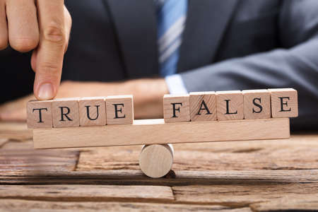Midsection of businessman with true and false wooden blocks on seesaw at desk