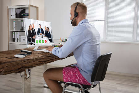 Homme d'affaires vêtu d'une chemise et d'un short-pantalons ayant un appel vidéo sur ordinateur au Home Office Banque d'images - 84270234