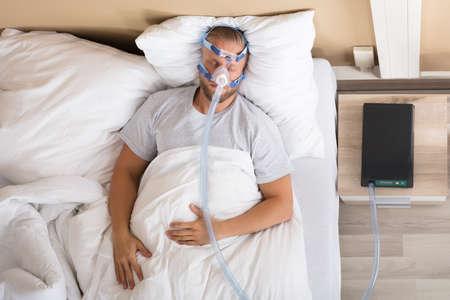 Jonge man liggend op bed met slaapapneu en CPAP-machine Stockfoto - 84270285