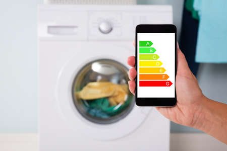 Closeup of mans hand using energy label on mobile phone against washing machine at home Stock Photo