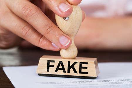 테이블에 문서 가짜 고무 스탬프를 찍는 사업가 확대 사진