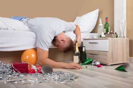 Young Man Lying On Bed With Messed Up Floor After Party Stock Photo