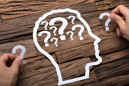 Cropped image of businessman holding question marks by paper head outline at wooden table