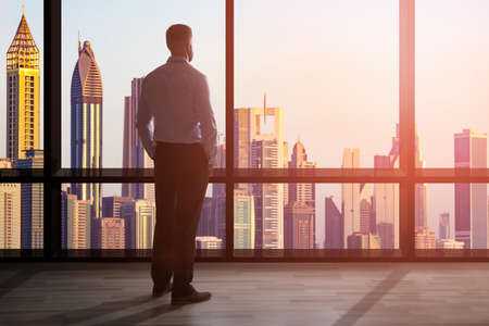 街の景観を見渡す高所の大きな窓に立っているビジネスマン