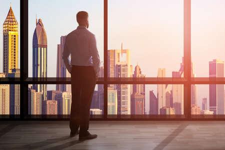 Uomo d'affari in piedi alla grande finestra di un ufficio alto che domina il paesaggio urbano