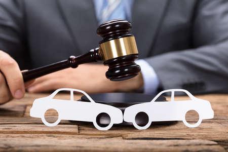 autoridad: Midsection de juez golpear mazo por los coches de papel en la mesa de madera