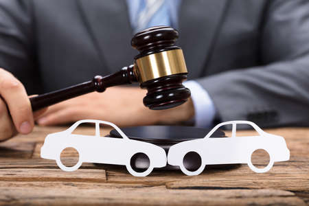 Midsection of judge hitting mallet by paper cars on wooden table Stock Photo - 84270332