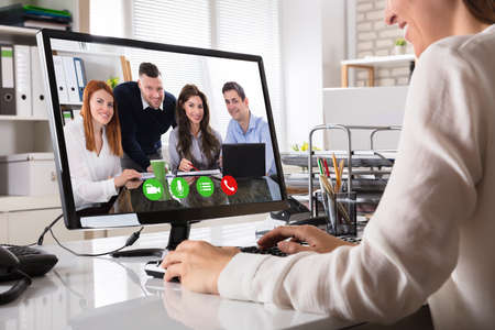 Close-up Of A Businesswoman Videoconferencing With Happy Male And Female Colleague On Computer Stock Photo