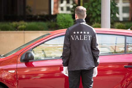 빨간 차 앞에 서있는 대리인의 후면보기 스톡 콘텐츠