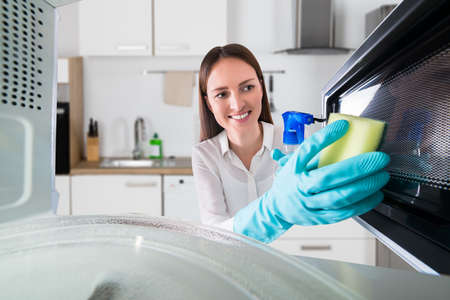 Young Woman Cleaning Microwave Oven With Spray Bottle And Sponge