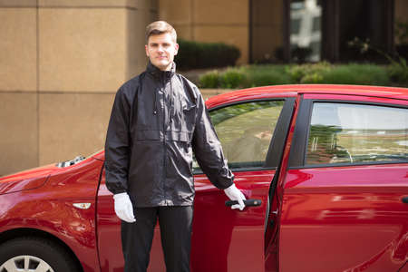 Portrait Of A Happy Young Male Valet Opening Red Car Door Stock Photo