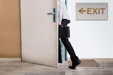 壁の出口標識と一緒に外を歩いての実業家