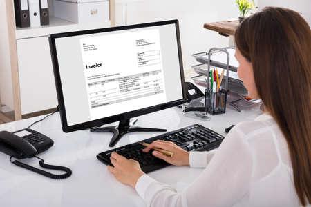 Close-up van een Onderneemster die Rekening op Computer op het Werk bekijken