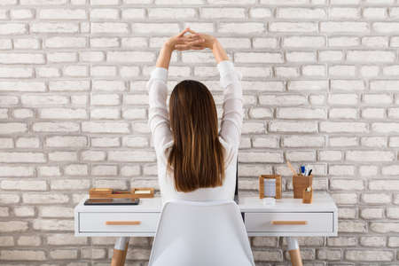 Rear View Of A Young Businesswoman Sitting On Chair Stretching Her Arms