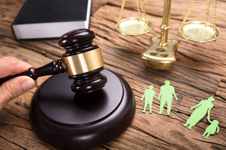 분리 된 종이 가족과 법의 규모로 나무 테이블에 망치를 치는 판사 스톡 콘텐츠