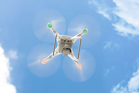 Low angle view of drone flying against blue sky Stock Photo