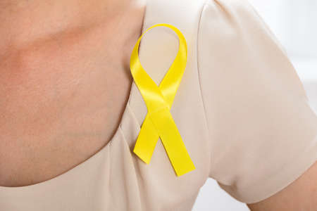 autoimmune: Close-up Of A Woman With Gold Ribbon To Support Childhood And Bladder Cancer Stock Photo