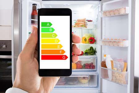 Primer plano de la mano del hombre usando la etiqueta energética en el teléfono móvil contra el refrigerador en el hogar
