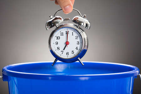 hands  hour: Cropped hand of businessman throwing alarm clock in blue bucket against gray background