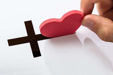 Main en insérant la forme de coeur dans la fente de Crucifix sur fond blanc
