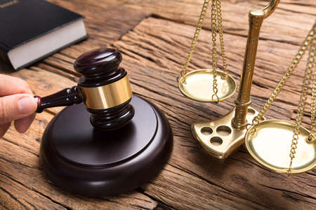 Cropped hand of judge hitting mallet by justice scale on wooden table in courtroom Stock Photo