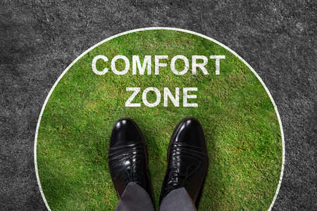 コンフォート ゾーン テキストと緑と灰色のカーペットの上に立っての実業家