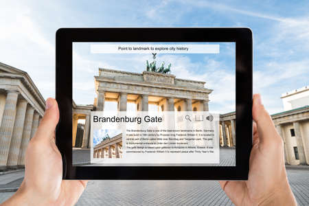Closeup of tourist taking picture of Brandenburg Gate from digital tablet