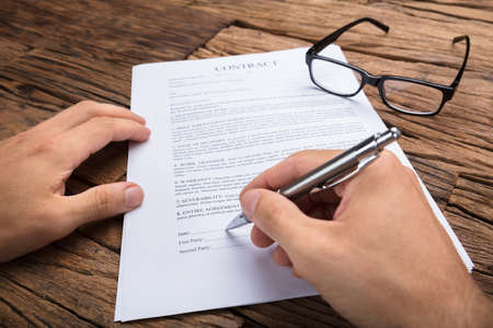 Cropped hands of businessman signing contract at wooden table Stock Photo