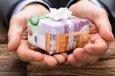 Cropped image of businessman holding gift box made from euro papernotes at wooden table Stock Photo