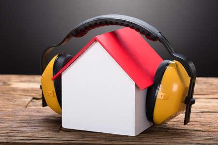 Close-up van modelhuis met oorbeschermers op houten lijst tegen zwarte achtergrond Stockfoto
