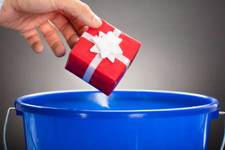 Cropped hand of businessman throwing gift box in blue bucket against gray background