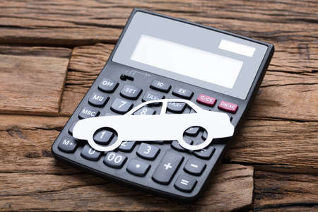 High angle view of paper car on calculator at wooden table
