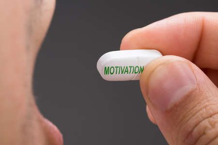 word of mouth: Cropped image of man having motivation pill against gray background