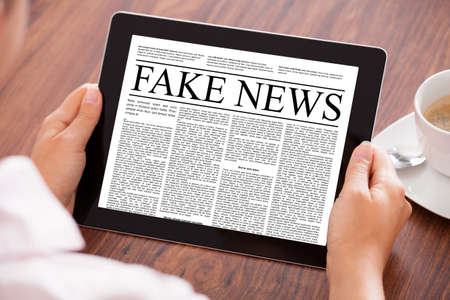 Cropped image of businesswoman reading fake news on digital tablet at table in office Stock Photo - 84587961