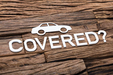 High angle view of paper car with covered and question mark sign on wooden table Stock Photo