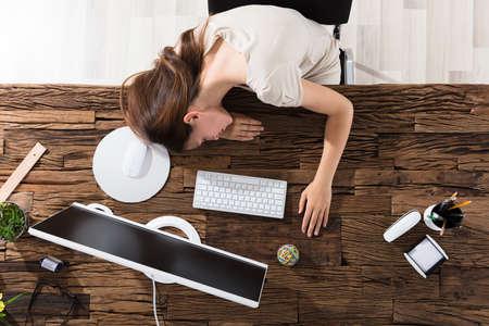 Vue en haut de la jeune femme d'affaires épuisée Dormir au bureau Banque d'images
