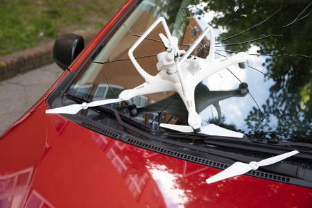 Closeup of damaged white drone on broken car windshield Stock Photo