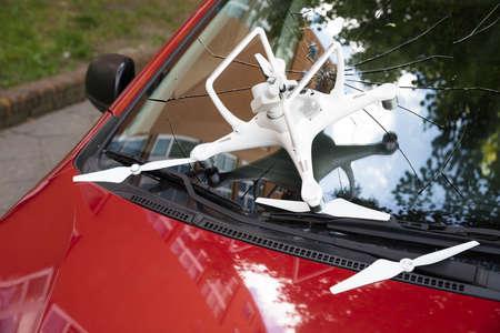 Primer plano de drone blanco dañado en el parabrisas roto del coche