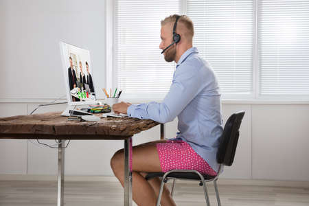 Businessman Dressed In Shirt And Shorts Having Video Call On Computer In The Home Office