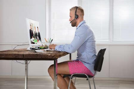 Uomo d'affari vestito in camicia e pantaloncini Avere chiamata video sul computer nel ufficio domestico Archivio Fotografico - 84587998
