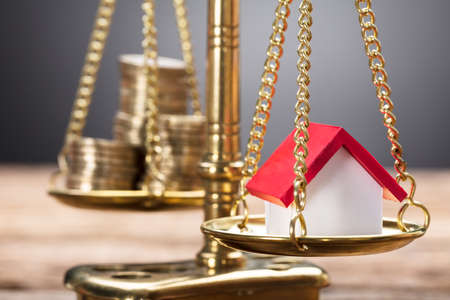 Closeup of model home and coins on golden weighing scale against gray background Stock Photo