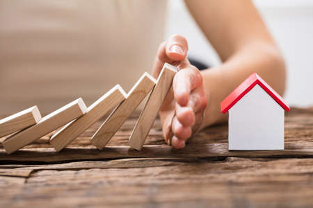 Close-up Of A Human Hand Stopping The Wooden Blocks From Falling On House Model Stock Photo - 84588021