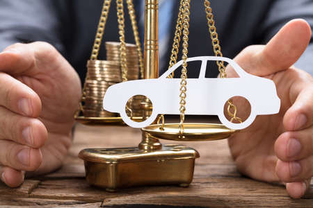 Businessman covering paper car and coins on golden weighing scale at wooden table Stock Photo - 84588022