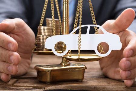 Zakenman die papierauto en munten op gouden weegschaal op houten tafel bedekt Stockfoto