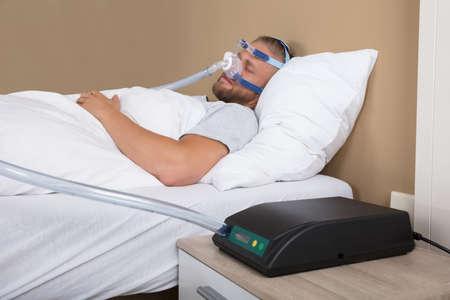 Young Man Lying On Bed With Sleeping Apnea And CPAP Machine