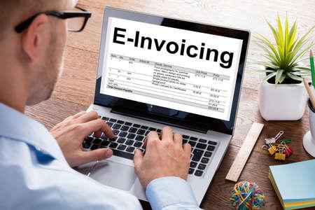 Imagen recortada del hombre de negocios que prepara la factura de factura electrónica en la computadora portátil en el escritorio en la oficina Foto de archivo